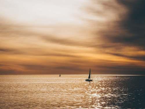 ocean silhouette of sailboat sailing on the ocean sea