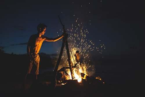 campfire topless man lighting bonfire fire