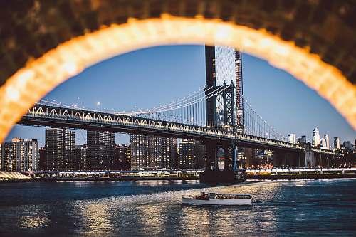 bridge boat below bridge during dusk metropolis