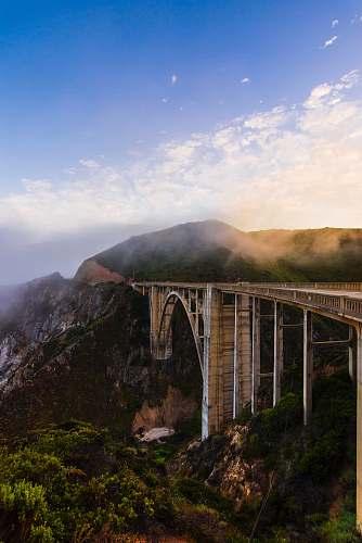 bridge gray concrete bridge over green mountains during daytime architecture