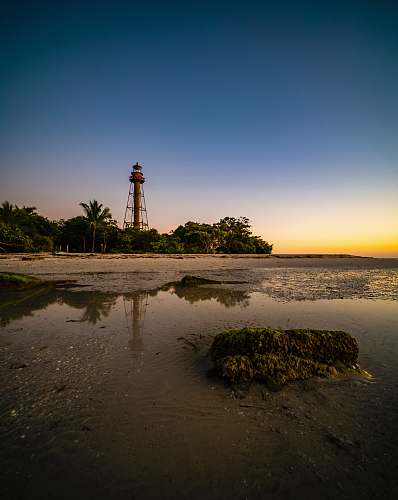 architecture lighthouse on brown sand near body of water during sunset tower