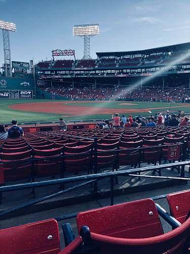 human people sitting inside baseball arena during daytime person
