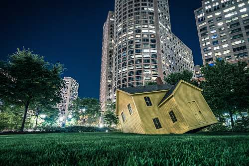 housing yellow house on green grass overlooking buildings at nighttime boston