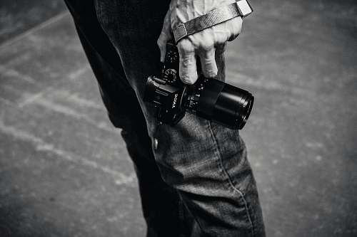 black-and-white grayscale photo of person holding DSLR camera ferry building