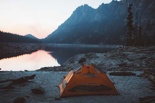 tent orange and gray camping tent near body of water leisure activities