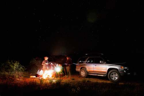 car people standing near vehicle and dome tent campfire