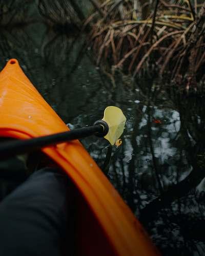 boat person riding orange kayak rowboat