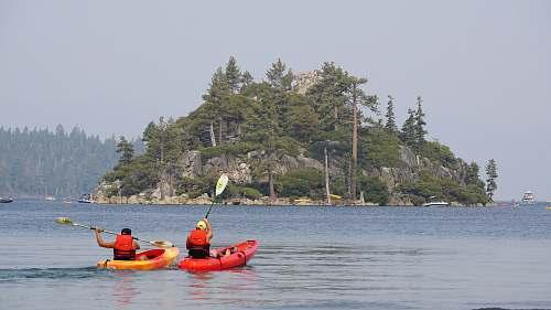 boat two person kayaking on water near islet kayak