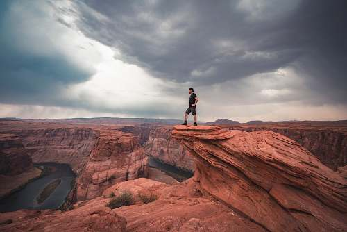 mountain man standing on top of horseshoe bend at Arizona nature