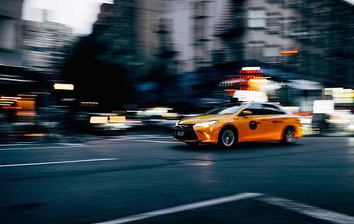 cab orange coupe running on gray street during daytiem taxi