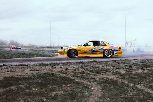 vehicle yellow and blue coupe drifts on black asphalt road during daytime automobile