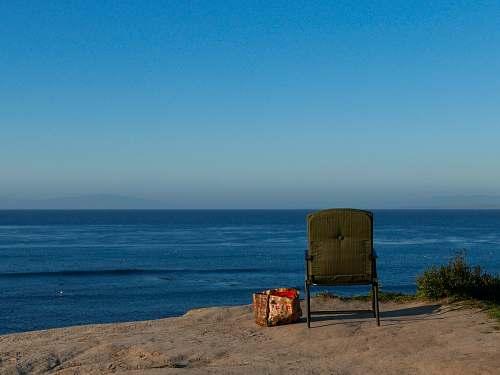 furniture brown armchair near sea shore horizon