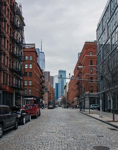 street vehicles on roadway between high rise buildings at daytime tribeca