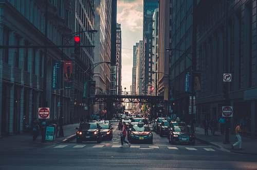 urban woman crossing pedestrian lane towards building during daytime chicago