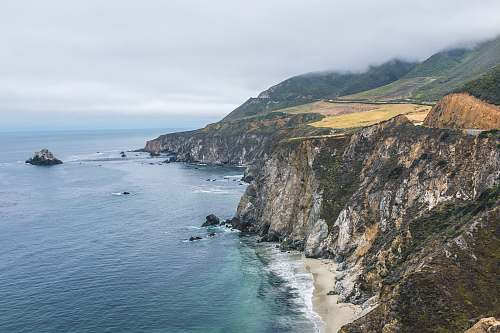 outdoors aerial photography of mountain beside body of water promontory