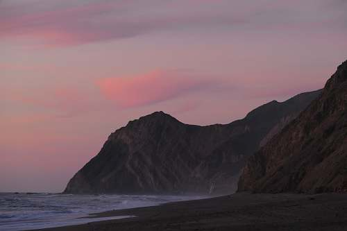 ocean mountain beside body of water coast