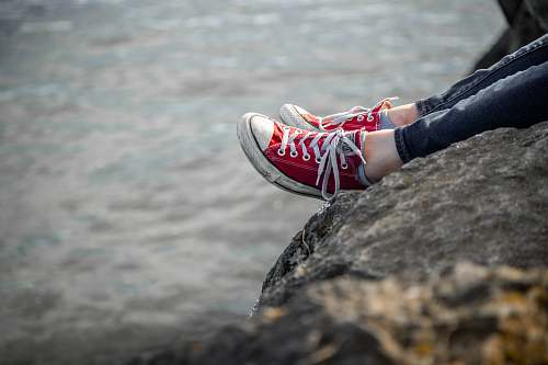 footwear person sitting on rock shoe