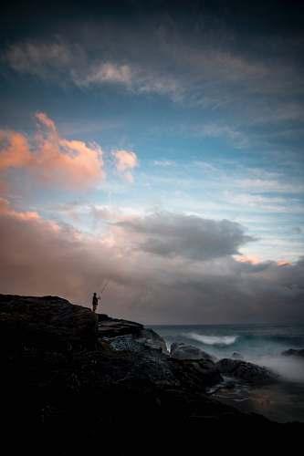 ocean man standing on cliff fishing during daytime sky
