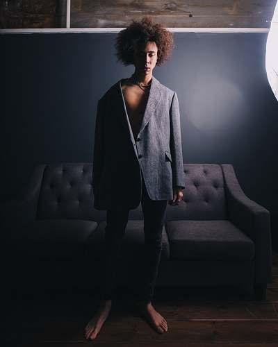 suit man standing wearing black blazer behind sofa overcoat