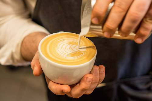 beverage person pouring cream on coffee drink