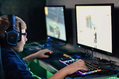 electronics boy wearing headset playing computer game monitor