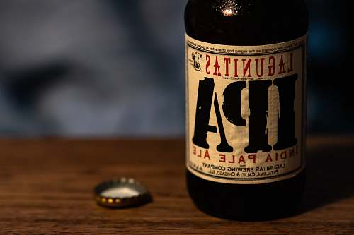 beer selective focus photography of Lagunitas IPA India Pale Ale bottle with bottle crown on tabole beverage