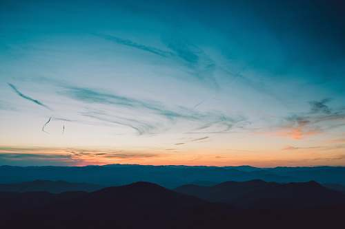 sunset silhouette of mountains under golden hour dawn