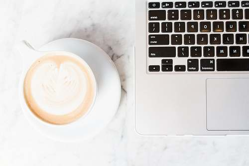 keyboard cappuccino on teacup and coaster beside a MacBook cup