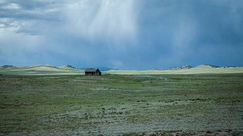 grassland green grass field under white cloudy sky during daytime outdoors