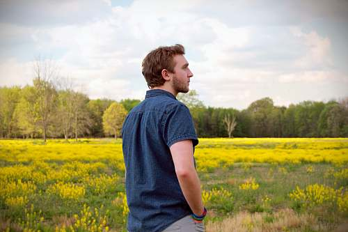grassland man in blue polo shirt and grey pants standing in yellow flower field outdoors