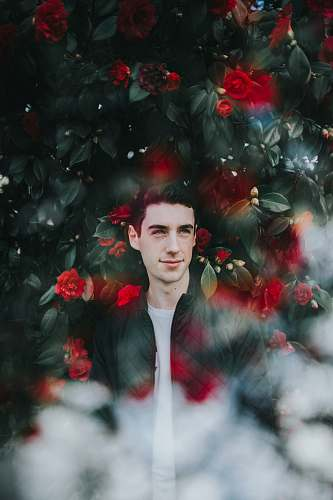 rose man in black zip-up jacket standing in frond of green plants and red flowers blossom