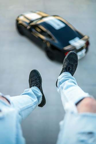 apparel shallow focus photography unknown person in blue distressed jeans and black sneakers clothing