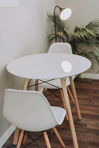 table round white wooden 3-piece bistro set beside floor lamp dining table