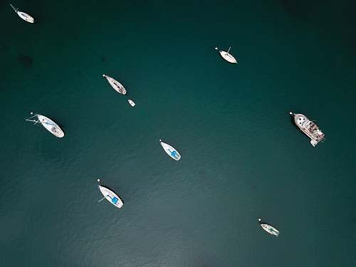 sea aerial photo of boats on calm body of water during daytime ocean