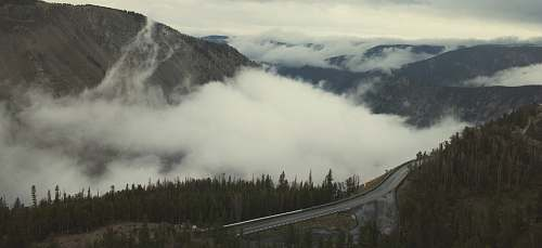 mountain aerial photo of road and mountains with white fogs at daytime beartooth highway