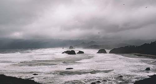 nature rock formations between sea under gray sky sea
