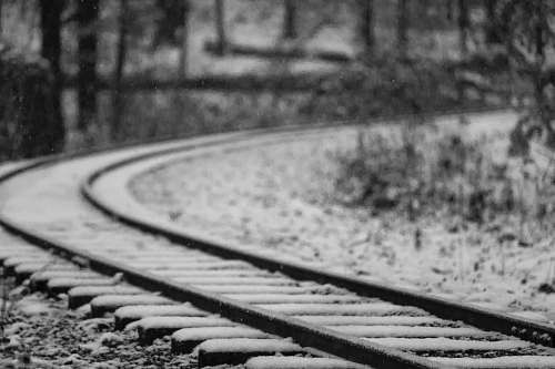 black-and-white selective focus photography of black metal railroad covered with snow railway