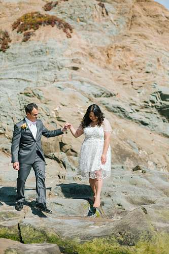person couple walking beside rock formation suit