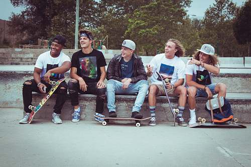 people five group of men sitting together with their skateboards person