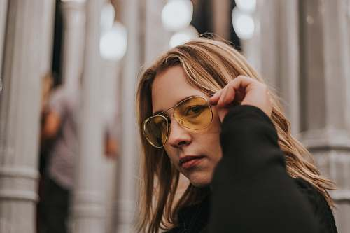 person focus of photo of woman holding her sunglasses people