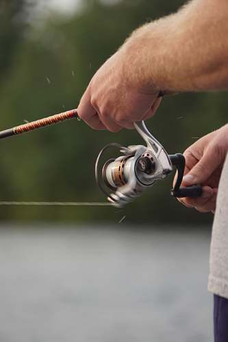 person focus photo of man holding fishing rod and fishing reel people