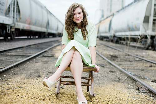 person girl sitting on chair between train tracks during day people
