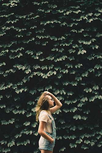 person girl standing beside tree holding her hair people