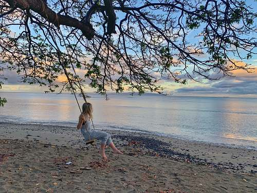 person girl wearing blue romper pants on swing hanging on tree besides seashore 800 olowalu village rd