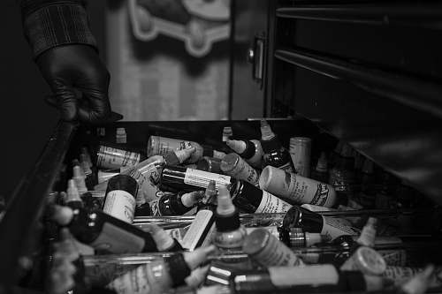 person grayscale photography of drawer full of bottles black-and-white