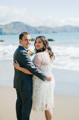 person groom and bride standing on seashore people
