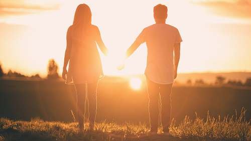 person man and woman holding hands white facing sunset people