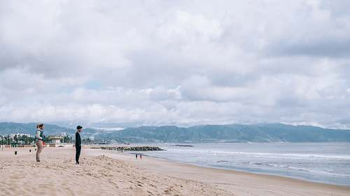 person man and woman standing on sand near ocean during daytime sea