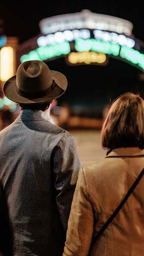 people man and woman standing on street hat