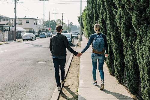 person man and woman walking on pathway during daytime people